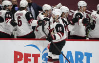 Arizona Coyotes center Derick Brassard, front, is congratulated as he passes the team box after scoring a goal against the Colorado Avalanche in the first period of an NHL hockey game Monday, March 8, 2021, in downtown Denver. (AP Photo/David Zalubowski)