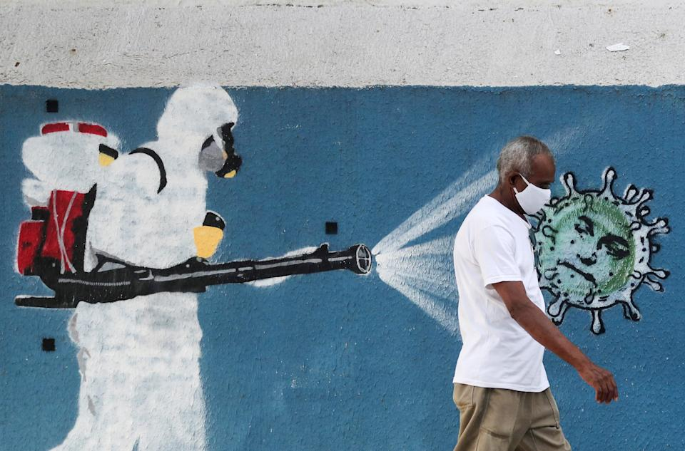 A man walks next to a graffiti depciting a cleaner wearing protective gear spraying viruses with the face of Brazil's President Jair Bolsonaro amid the coronavirus disease (COVID-19) outbreak, in Rio de Janeiro, Brazil, June 12, 2020. REUTERS/Sergio Moraes     TPX IMAGES OF THE DAY