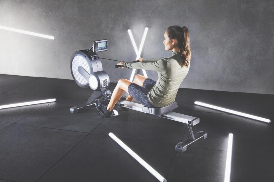 A woman wearing exercise clothing uses an Air resistance rower