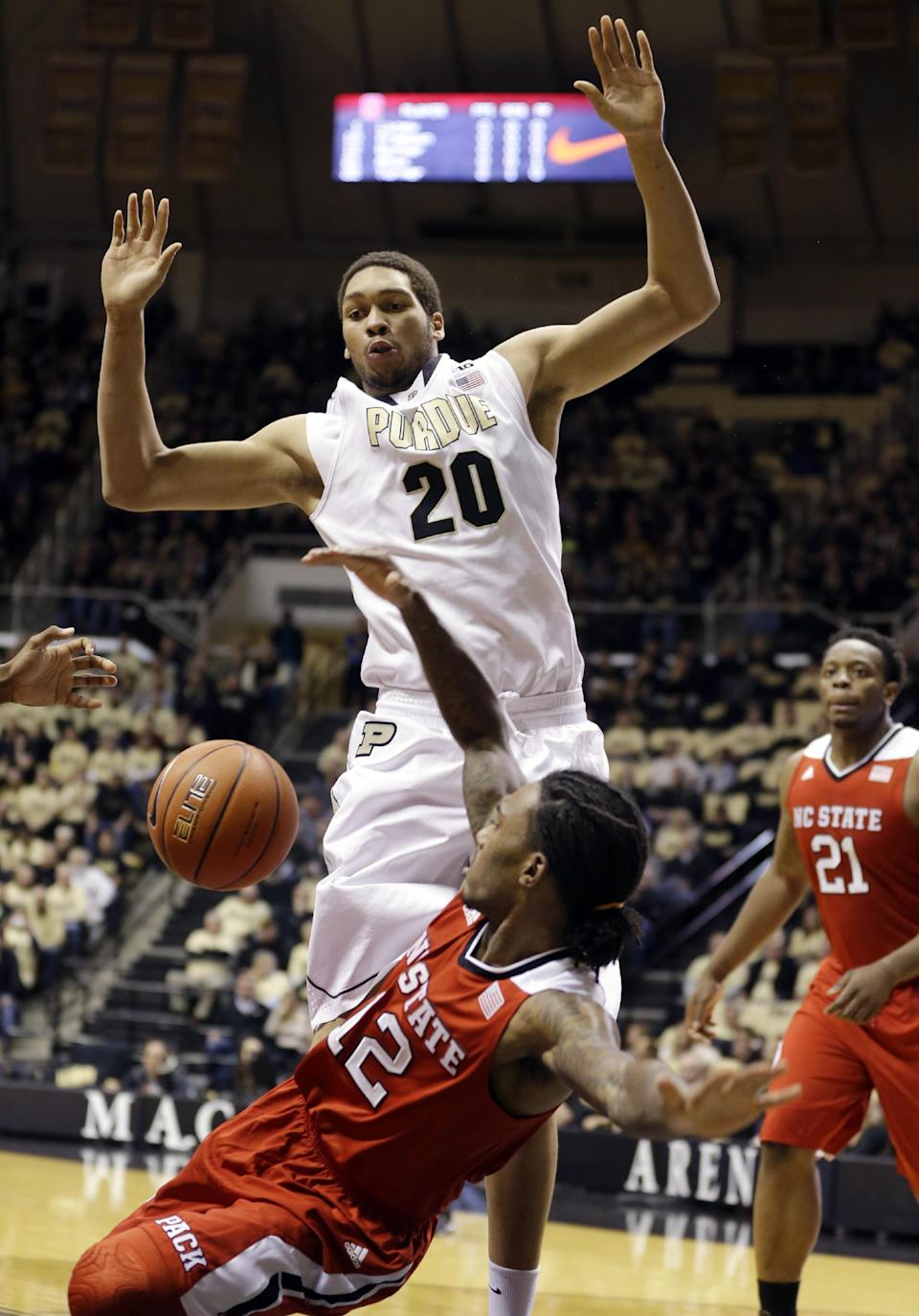 Purdue center A.J. Hammons, top, fouls North Carolina State guard Anthony Barber in the first half of an NCAA college basketball game in West Lafayette, Ind., Tuesday, Dec. 2, 2014. (AP Photo/Michael Conroy)