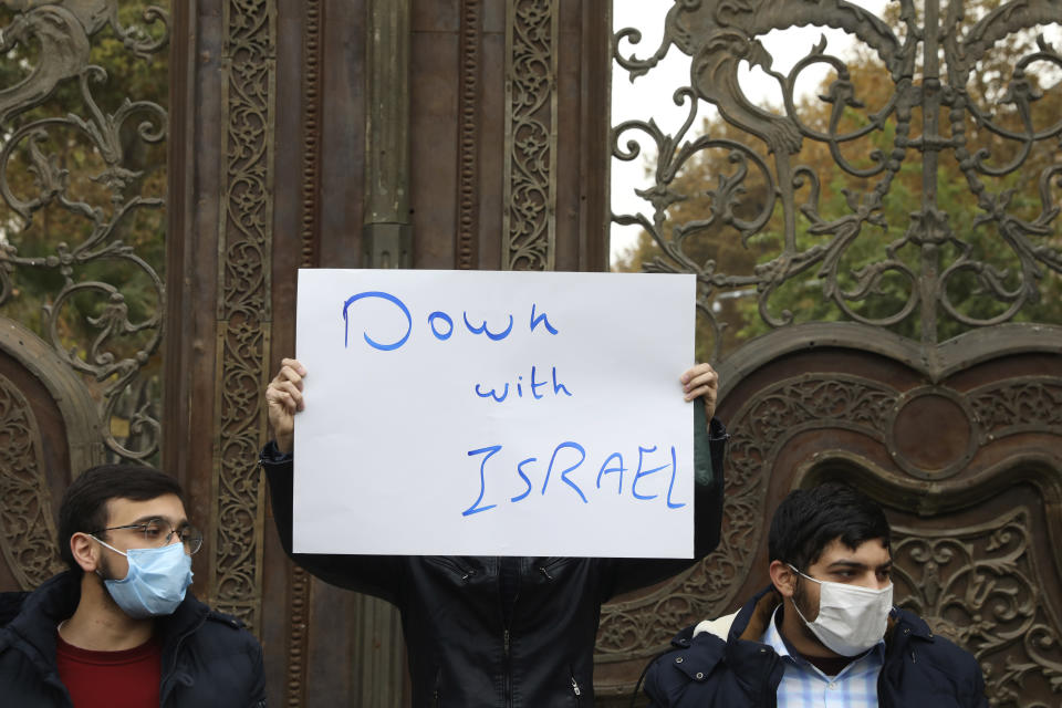 A protester holds an anti-Israeli placard during a gathering in front of Iranian Foreign Ministry on Saturday, Nov. 28, 2020, a day after the killing of Mohsen Fakhrizadeh an Iranian scientist linked to the country's nuclear program by unknown assailants near Tehran. (AP Photo/Vahid Salemi)