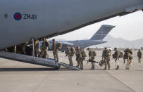 In this handout photo provided by the Ministry of Defence, UK military personnel onboard a A400M aircraft departing Kabul, Afghanistan, Saturday, Aug. 28, 2021. Britain has ended evacuation flights from Kabul airport and begun bringing U.K. troops home. Britain's defense ministry said the final flight for Afghan citizens had left Kabul. Further flights over the weekend will bring home British troops and diplomats and a few remaining civilians. (Jonathan Gifford/Ministry of Defence via AP)