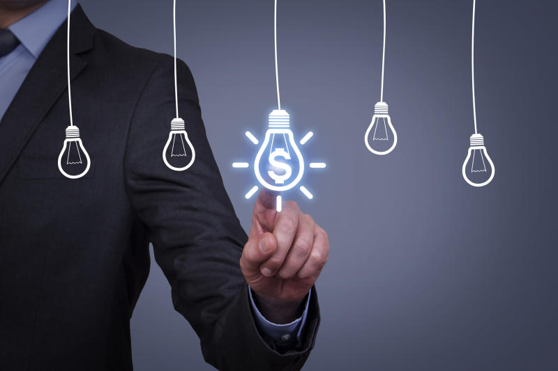 Businessman pointing to a drawing of a light bulb with a dollar sign on it with four other liight bulbs drawn to the left and right.