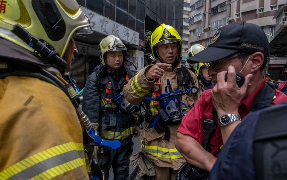 Firefighters could be seen spraying water into the middle floors - Getty Images AsiaPac