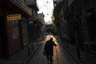 An elderly man walks along a nearly empty street of Psiri, in central Athens, on Tuesday, Dec. 1, 2020. Outbreaks of COVID-19 prompted Greece to impose two countrywide lockdowns, in the spring, keeping infection rates low, and in the fall as authorities scrambled to cope with a rampant rise in cases. (AP Photo/Petros Giannakouris)