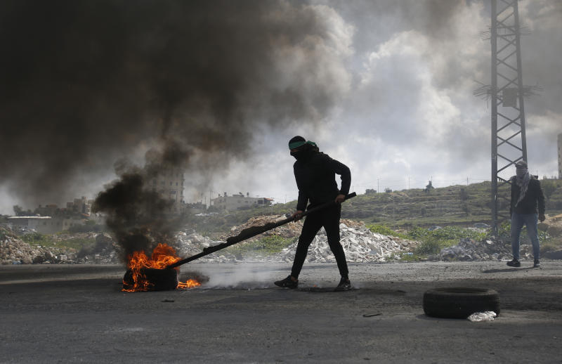 A Palestinian protester burns a tyre during a clashes with Israeli troops during demonstration in support of Palestinian prisoners held in Israeli jails at checkpoint Bet El near the West Bank city of Ramallah , Wednesday, March 27, 2019.(AP Photo/Majdi Mohammed)
