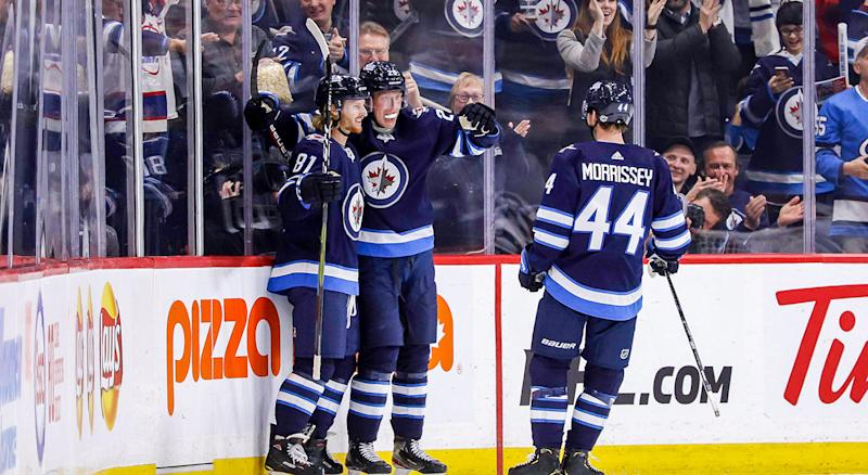 WINNIPEG, MB - OCTOBER 10: Kyle Connor #81, Patrik Laine #29 and Josh Morrissey #44 of the Winnipeg Jets celebrate a third period goal against the Minnesota Wild at the Bell MTS Place on October 10, 2019 in Winnipeg, Manitoba, Canada. (Photo by Darcy Finley/NHLI via Getty Images)