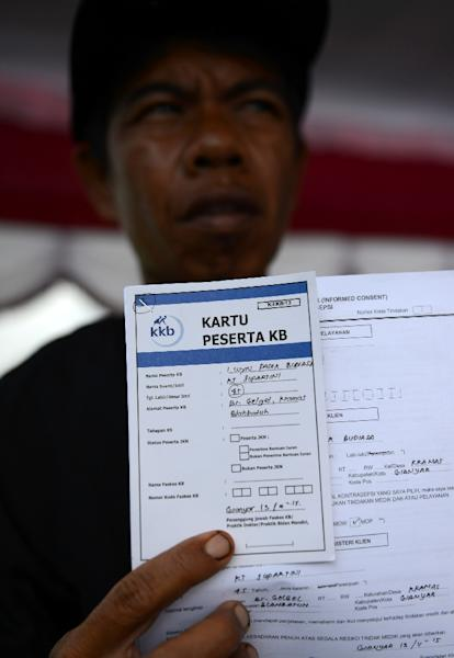 A man shows his registration for a vasectomy operation in Gianyar on the island of Bali on November 13, 2015 (AFP Photo/Sonny Tumbelaka)