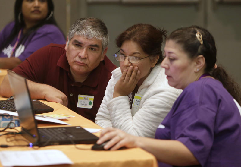 In this photo taken Saturday, Nov. 9, 2013 Carlos Barajas, left, and his wife, Martha, center, look over their health insurance plan options with volunteer Elizabeth Lira, at a health fair in Sacramento, Calif. The lackluster showing for President Barack Obama's health care overhaul could foreshadow trouble for the embattled program. The plan relies on younger, healthier Americans, who are in less need of health care, to sign-up to cover the costs of expanding coverage to those with serious problems.(AP Photo/Rich Pedroncelli)