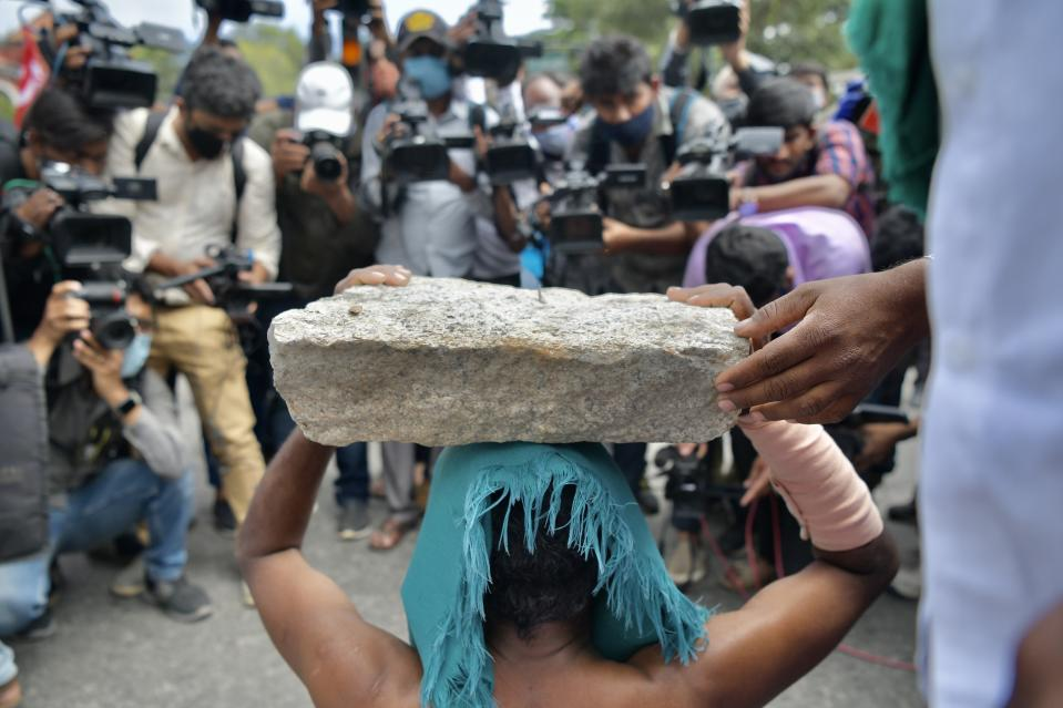 Media personnel document an activist from a farmer right organisation during a protest following the recent passing of agriculture bills in the Lok Sabha (lower house), in Bangalore on September 25, 2020. - Angry farmers took to the streets and blocked roads and railways across India on September 25, intensifying protests over major new farming legislation they say will benefit only big corporates. (Photo by Manjunath Kiran / AFP) (Photo by MANJUNATH KIRAN/AFP via Getty Images)
