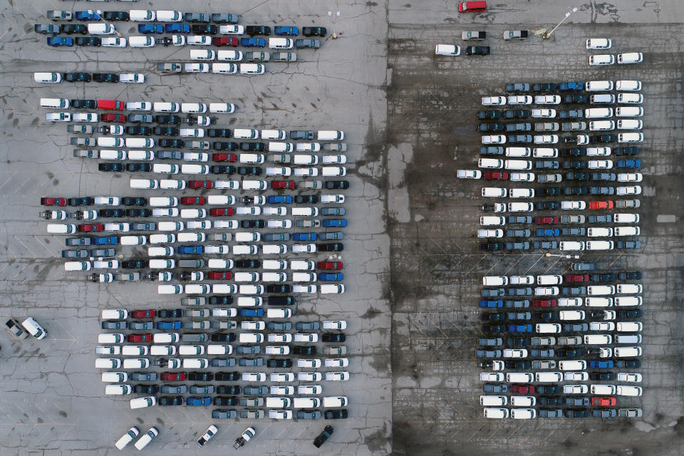 In this aerial photo, mid-sized pickup trucks and full-size vans are seen in a parking lot outside a General Motors assembly plant where they are produced Wednesday, March 24, 2021, in Wentzville, Mo.   The global shortage of semiconductors is forcing General Motors to further cut production at six North American factories as chip supplies seem to be growing tighter. The shutdowns likely will crimp dealer inventory of vehicles made at the plants, but GM says it has managed to keep factories humming that make hot-selling and profitable full-size pickup trucks and SUVs.  (AP Photo/Jeff Roberson)
