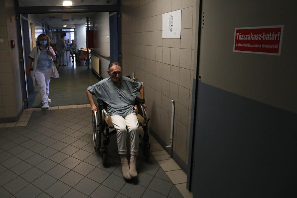 An elderly homeless man uses a wheelchair at the hospital for the homeless in Budapest, Hungary, Wednesday, April 14, 2021. A bitter conflict has emerged between Hungary's right-wing government and the liberal leadership of the country's capital city over a hospital for the homeless that may soon have to close. The Budapest hospital provides medical and social services and shelter to more than 1,000 people annually. But the Hungarian government has ordered it to vacate the state-owned building it occupies. Budapest's mayor says the eviction will risk the lives of the hospital's homeless patients as Hungary struggles with a deadly COVID-19 surge. (AP Photo/Laszlo Balogh)