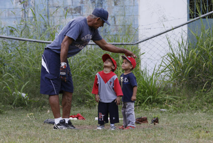 In this Oct. 25, 2012 photo, baseball coach Jose Torres instructs two young boys at a baseball school in Maracay, Venezuela. Many of the boys are inspired by the example of Detroit Tigers slugger Miguel Cabrera, who learned the game on this very field. Their baseball school in the poor neighborhood where Cabrera grew up is one of many across Venezuela, a web for training young ballplayers that has made the country a powerhouse in the U.S. major leagues. (AP Photo/Ariana Cubillos)