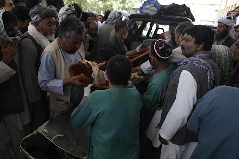 Afghan health officials carry the body of an aid worker into a hospital in Mazar-i-Sharif on June 2, 2015 (AFP Photo/Bashir Dawodi)
