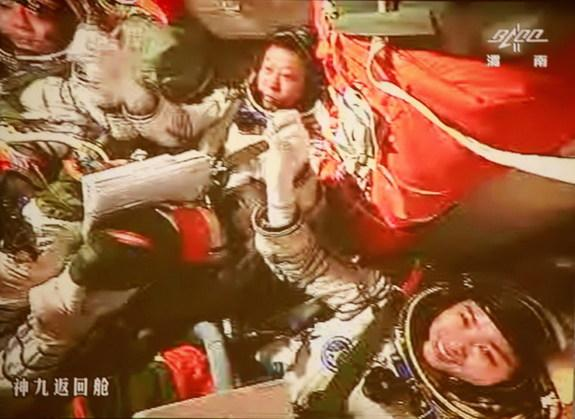 The three astronauts aboard China's Shenzhou 9 spacecraft grasp hands to celebrate their successful manned docking with the Tiangong 1 orbiting module on June 24, 2012. At center is astronaut Liu Wang, who piloted the successful docking. Missio