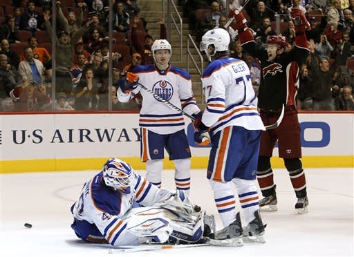 Edmonton Oilers' Devan Dubnyk (40) gives up a goal to Phoenix Coyotes' Radim Vrbata, as Coyotes' Martin Hanzal, of the Czech Republic, back right, celebrates, as Oilers' Ladislav Smid, of the Czech Republic, and Tom Gilbert (77) look at one another in the second period in an NHL hockey game Thursday, Dec. 15, 2011, in Glendale, Ariz.(AP Photo/Ross D. Franklin)