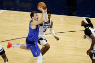 Dallas Mavericks guard Luka Doncic (77) passes in front of Minnesota Timberwolves forward Jaden McDaniels (3) and center Naz Reid (11) in the second quarter during an NBA basketball game, Sunday, May 16, 2021, in Minneapolis. (AP Photo/Andy Clayton-King)