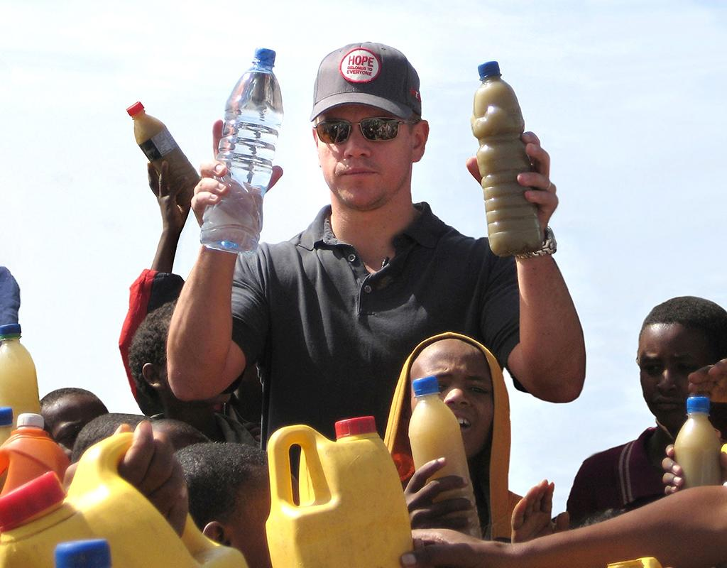 MEKELE, ETHIOPIA - APRIL 20:  In this handout image provided by PMK/HBH, ONEXONE Foundation Ambassador actor Matt Damon visits a well just outside Mekele, Ethiopia on April 20, 2009. In his right hand he holds a bottle of regular water, in his left is a bottle of dirty water local children in Mekele drink everyday.  (Photo by Handout/Getty Images) *** Local Caption *** Matt Damon