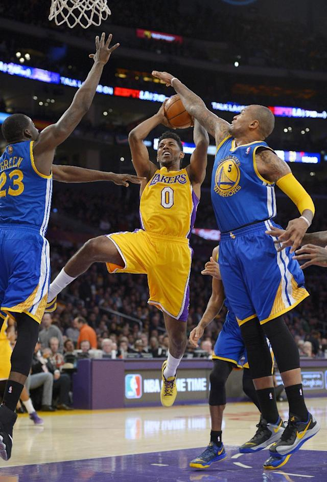 Los Angeles Lakers forward Nick Young, center, puts up a shot as Golden State Warriors forward Draymond Green, left, and forward Marreese Speights defend during the first half of an NBA basketball game, Friday, Nov. 22, 2013, in Los Angeles. (AP Photo/Mark J. Terrill)
