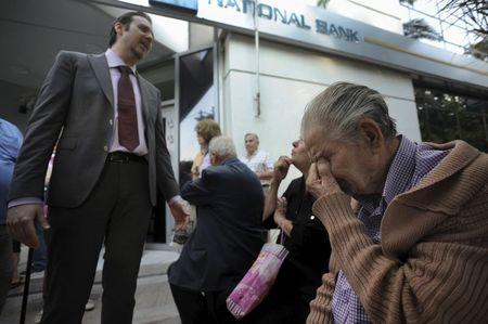 A bank manager explains the situation to pensioners waiting outside a branch of the National Bank of Greece hoping to get their pensions, in Thessaloniki