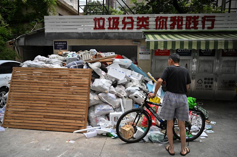 In this photo taken on July 11, 2019, a man looks at piled up garbage at a housing complex in the former French concession in Shanghai. - Shanghai on July 1 launched China's most ambitious garbage separation and recycling programme ever, as the country confronts a rising tide of trash created by increasingly consumptive ways. But the programme is the talk of China's biggest city for other reasons as well: confusion over rules and fines for infractions, and thousands of volunteers inspecting citizens' private garbage each day. (Photo by HECTOR RETAMAL / AFP) / TO GO WITH: China-environment-waste-recycling, FOCUS by Lianchao LAN and Dan MARTIN (Photo credit should read HECTOR RETAMAL/AFP via Getty Images)