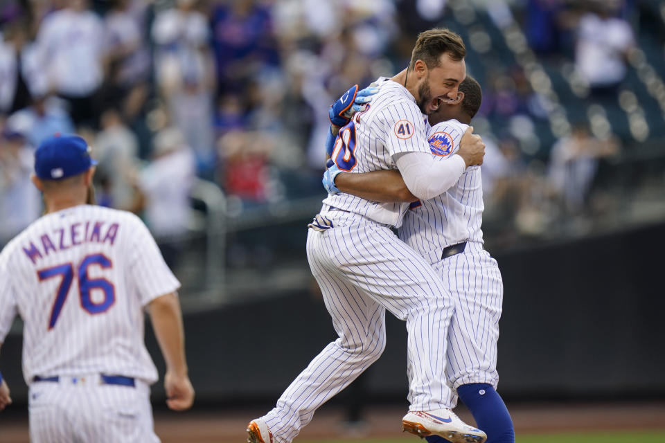 New York Mets' Michael Conforto (30) hugs Dominic Smith after Smith hit an RBI-single during the eighth inning of the first baseball game of a doubleheader against the Philadelphia Phillies, Friday, June 25, 2021, in New York. The Mets wo 2-1. (AP Photo/Frank Franklin II)