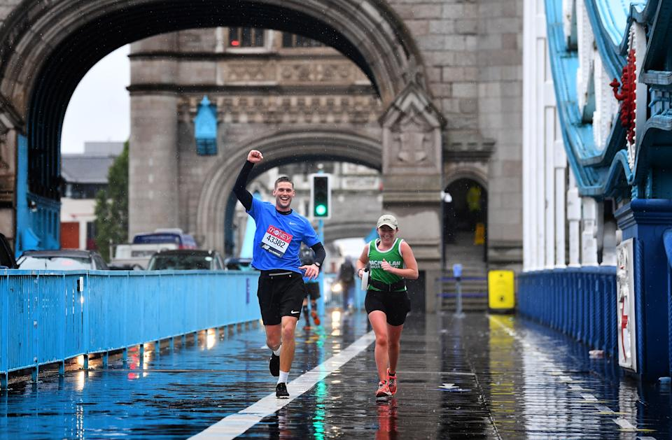 Runners wearing London Marathon running numbers cross Tower Bridge as some 45,000 people are running or walking the 40th London Marathon along their own 26.2-mile route around the UK, after the event originally planned for April 26 was postponed due to coronavirus. (Photo by Victoria Jones/PA Images via Getty Images)