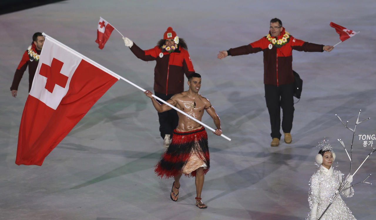 <p>Pita Taufatofua carries the flag of Tonga during the opening ceremony of the 2018 Winter Olympics in Pyeongchang, South Korea, Friday, Feb. 9, 2018. (AP Photo/Michael Sohn) </p>
