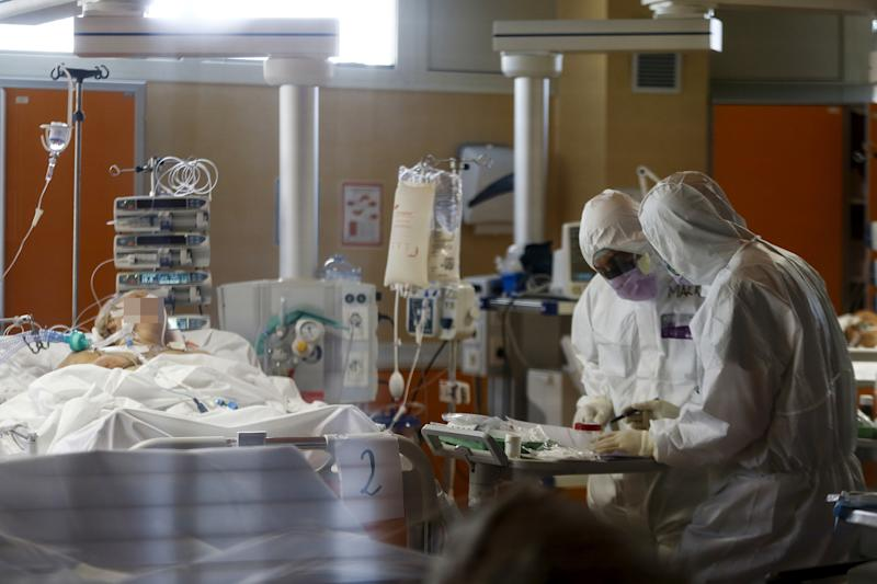 Medical workers in protective suits treat patients in an Intensive Care Unit in Italy. Source: Sipa USA