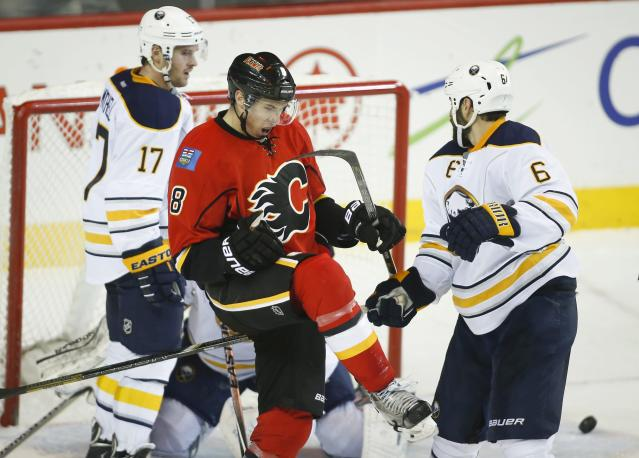 Buffalo Sabres' Torrey Mitchell, right, and Mike Weber, left, look on as Calgary Flames' Joe Colborne celebrates his goal during second period NHL hockey action in Calgary, Alberta, on Tuesday March 18, 2014. (AP Photo/The Canadian Press, Jeff McIntosh)