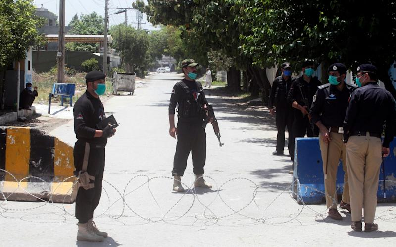 Pakistani police officers stand guard at a checkpoint of a restricted area to help contain the spread of the new coronavirus, in Peshawar, Pakistan - Muhammad Sajjad/AP
