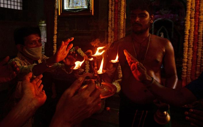 A Hindu priest holds a lamp as he gives blessing to devotees at a temple on the Tamil's holy month of Aadi during a lockdown in Chennai - AFP