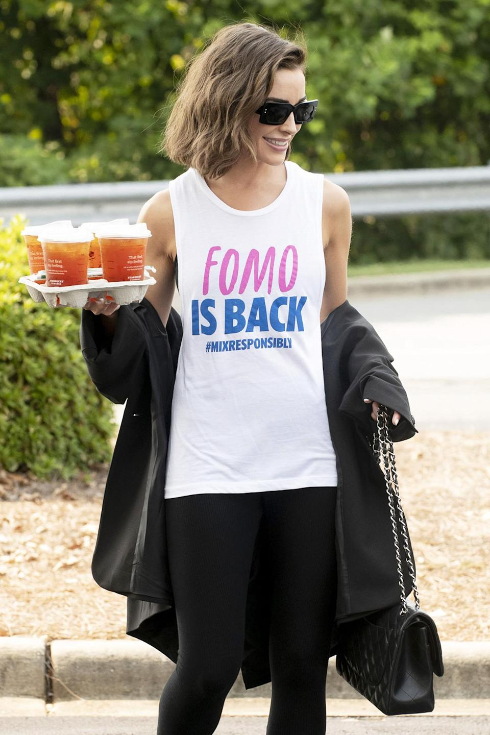 <p>Olivia Culpo picks up coffee while wearing an Absolut #MixResponsibly tank in Charlotte, North Carolina, on Sept. 16. </p>