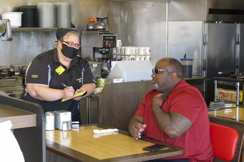 Corey Brooks, right, orders food at a Waffle House restaurant in Savannah, Georgia, on Monday, April 27, 2020. Restaurants statewide were allowed to resume dine-in service with restrictions after a month of being limited to takeout orders because of the coronavirus. (AP Photo/Russ Bynum)