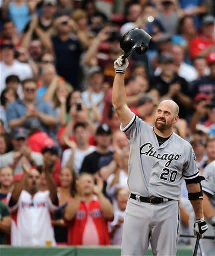 Chicago White Sox third baseman Kevin Youkilis tips his batting helmet to fans as he receives a standing ovation during the first inning of a baseball game against the Boston Red Sox at Fenway Park in Boston, Monday, July 16, 2012. Youkilis returned to Fenway, where he was a member of the 2004 and 2007 World Series Champion teams, for the first time since being traded. (AP Photo/Charles Krupa)