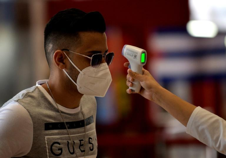 A passenger has his temperature checked at Havana's Jose Marti International Airport -- as the country reopens to tourists, the threat of imported coronavirus cases rises