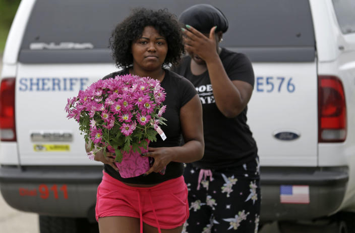 People bring flowers to the scene where the body of missing 6-year-old Ahlittia North was found in Harvey, La., Tuesday, July 16, 2013. Lisa North, the mother of the child, says Jefferson Parish authorities have found the body of her daughter in a Harvey trash bin. Ahlittia disappeared from her apartment late Friday night or early Saturday morning. North's husband Albert Hill said they were told the body was found in a trash bin not far from their apartment. (AP Photo/Gerald Herbert)