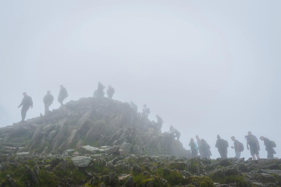 When UK relaxed pandemic lockdown rules in August 2020 it resulted in surge of ''stay-cation holidays''. Hikers awaits in a queue on foggy and misty day for their turn to access the peak of mount Snowdon to take a selfie.