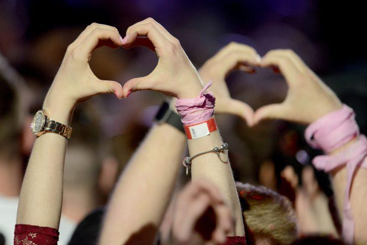 Fans making heart shapes with their hands at One Love Manchester concert. (Dave Hogan via AP)