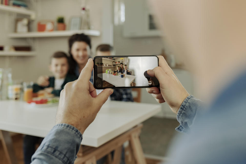 Father Take a Photo of His Family With Smartphone While Having Breakfast Together at Home. Family, Technology and People Concept
