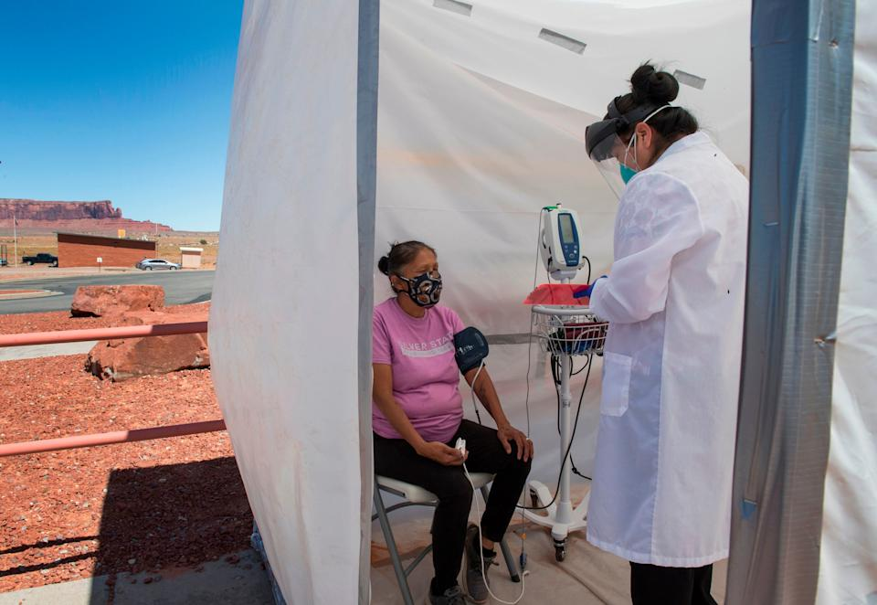 A nurse checks the vitals of a Navajo Indian woman at a COVID-19 testing center at the Navajo Nation town of Monument Valley in Arizona on May 21, 2020. Monument Valley would normally be teeming with tourists at this time of year -- instead it's become the latest COVID-19 hotspot inside the hard-hit Navajo Nation, America's biggest Native American territory. (Photo: MARK RALSTON via Getty Images)