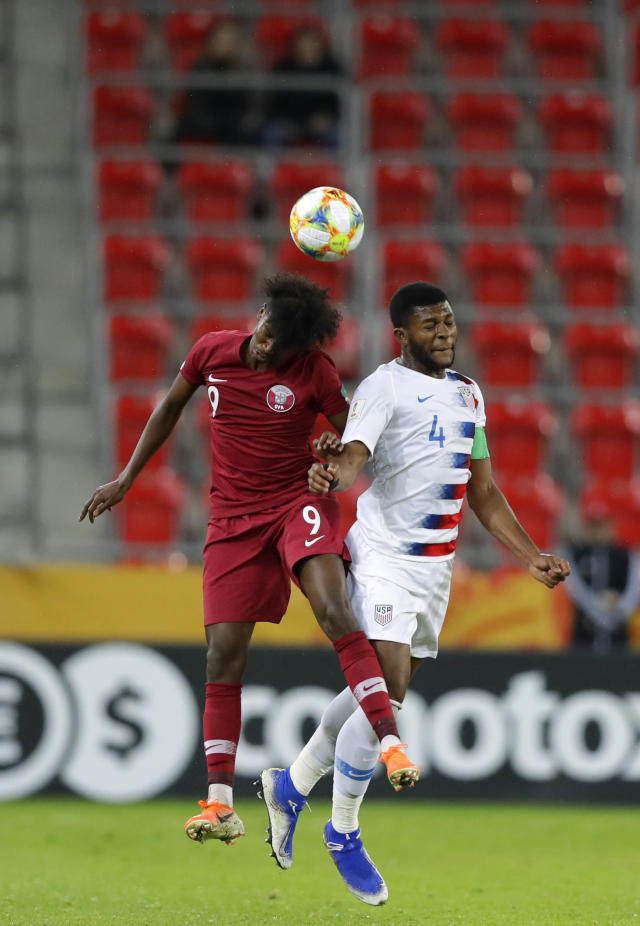 Qatar's Yusuf Abdurisag, left, duels for the ball with United States' Mark McKenzie during the Group D U20 World Cup soccer match between USA and Qatar, in Tychy, Poland, Thursday, May 30, 2019. (AP Photo/Sergei Grits)