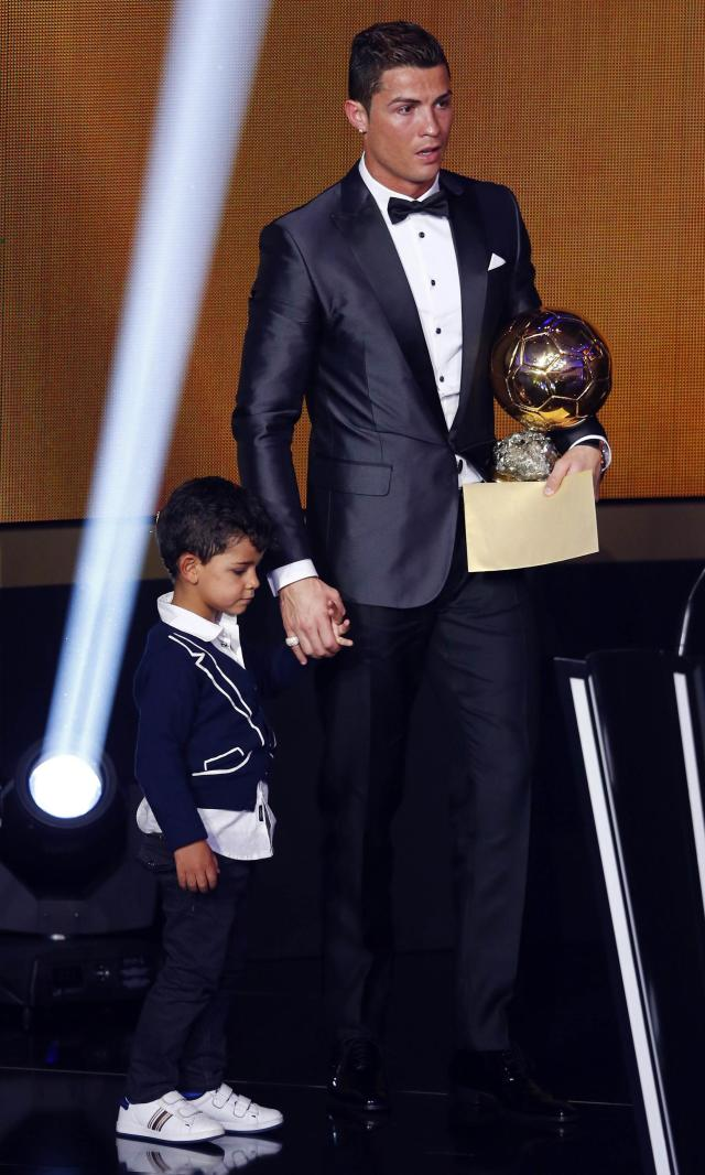 Portugal's Cristiano Ronaldo holds his trophy with his son Cristiano Ronaldo Jr after being awarded the FIFA Ballon d'Or 2013 in Zurich January 13, 2014. Portugal and Real Madrid forward Cristiano Ronaldo was named the world's best footballer for the second time on Monday, preventing his great rival Lionel Messi from winning the award for a fifth year in a row. REUTERS/Arnd Wiegmann (SWITZERLAND - Tags: SPORT SOCCER)