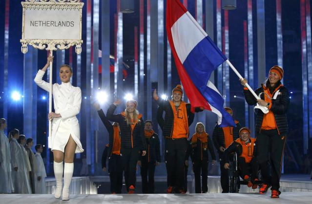 Bibian Mentel-Spee, flag-bearer of the Netherlands (R), leads her country's contingent during the opening ceremony of the 2014 Paralympic Winter Games in Sochi, March 7, 2014. REUTERS/Alexander Demianchuk (RUSSIA - Tags: OLYMPICS SPORT)