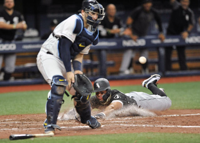 Chicago White Sox's Yoan Moncada, right, scores the game-winning run ahead of the throw to Tampa Bay Rays catcher Mike Zunino during the 11th inning of a baseball game Saturday, July 20, 2019, in St. Petersburg, Fla. The White Sox beat the Rays 2-1. (AP Photo/Steve Nesius)