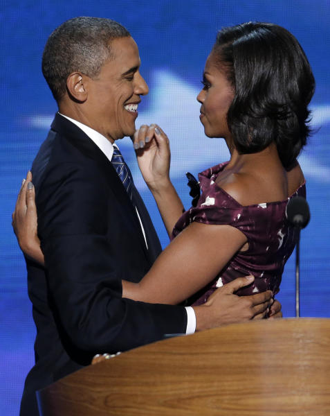 CORRECTS IDENTITIES - President Barack Obama hugs his wife Michelle before addressing the Democratic National Convention in Charlotte, N.C., on Thursday, Sept. 6, 2012. (AP Photo/J. Scott Applewhite)
