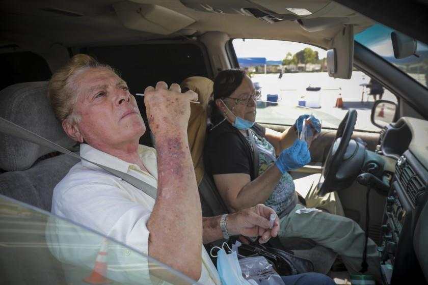 SANTA ANA , CA - AUGUST 22: Daniel Mendoza, left, and Linda Mendoza take a coronavirus test at a drive-in free COVID-19 testing site established by City of Santa Ana and Rancho Santiago Community College district in Santa Ana College parking lot on Saturday, Aug. 22, 2020 in Santa Ana , CA. (Irfan Khan / Los Angeles Times)