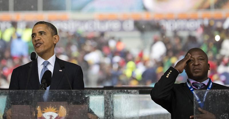 FILE - In this file photo from Dec.10, 2013, Thamsanqa Jantjie, right, interprets in sign language for President Barack Obama during his remarks at a memorial service at FNB Stadium in honor of Nelson Mandela in Soweto, near Johannesburg. The South African government says it is aware of reports that Jantjie faced a murder charge a decade ago, and says he is being investigated. (AP Photo/Evan Vucci, File)