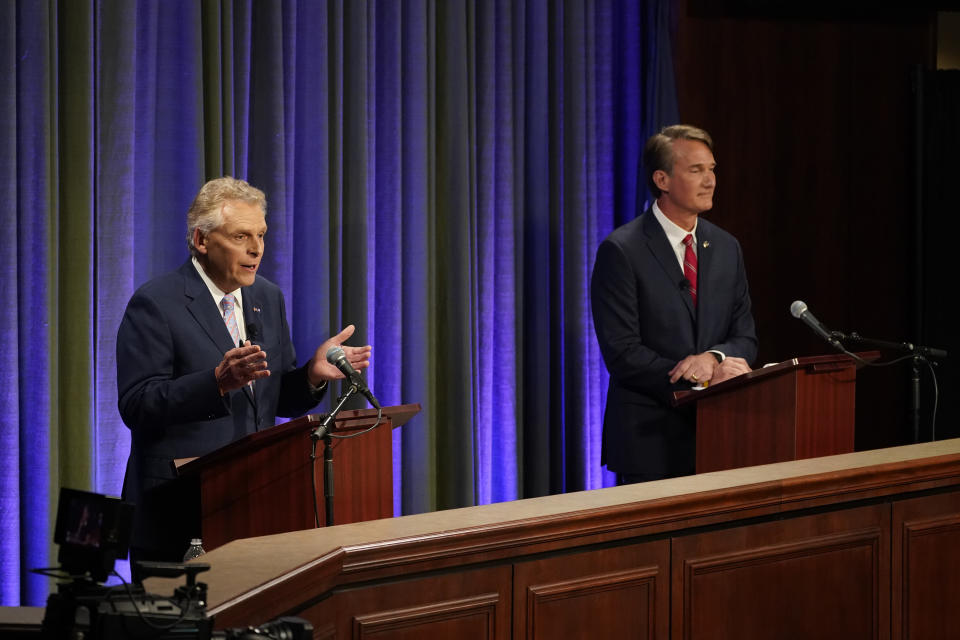 Democratic gubernatorial candidate and former governor Terry McAuliffe, left, gestures as his Republican challenger, Glenn Youngkin, looks on during a debate at the Appalachian School of Law in Grundy, Va., Thursday, Sept. 16, 2021. (AP Photo/Steve Helber)