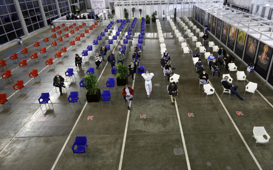 People sit, after receiving a COVID-19 vaccine at Belgrade Fair makeshift vaccination center, in Belgrade, Serbia, Monday, Jan. 25, 2021. Serbia were the first European country to receive the Chinese Sinopharm's vaccine for mass inoculation programmes. (AP Photo/Darko Vojinovic)